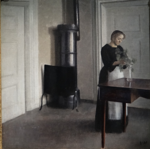 Interieur avec femme arrangeant des fleurs dan sun vase Hammer 1900.jpg